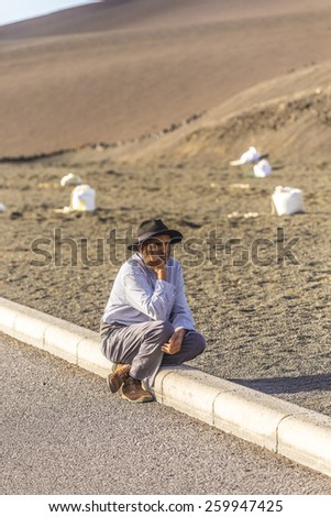 YAIZA, SPAIN - NOV 15, 2014: local camel riding man sits down and waits for tourists in Yaiza, Spain. Camel riding in Timanfaya national park is a must for tourists in Lanzarote. - stock photo