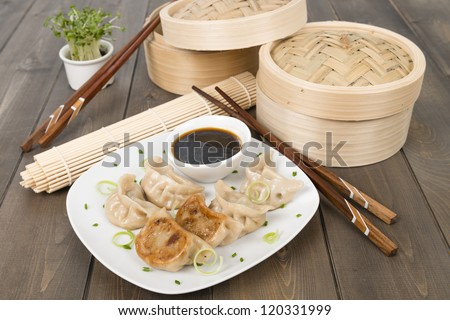 Yaki-Gyoza - Japanese pan-fried dumplings served with a soy based dipping sauce. Dark wood background. - stock photo