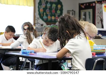Yakima, Washington / USA - October 17, 2017:  A classroom of kindergarten students concentrate hard on their school work.