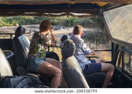 YALA NATIONAL PARK, SRI LANKA - MARCH 4, 2014: Tourists taking photos from jeep during safari tour in the Yala park. Yala is the second largest national park in Sri Lanka. - stock photo