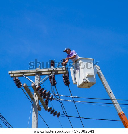 YALA, THAILAND - JUNE 7 : Officer of The Provincial Electricity Authority (PEA ,YALA) performing maintenance work in a basket for electric wiring on blue sky on JUNE 7, 2014 at YALA, THAILAND.