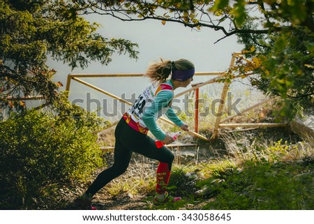 Yalta, Russia - November 4, 2015: girl athlete running through forest, in her hands a bottle of water isotonic during mountain marathon Tauris - stock photo