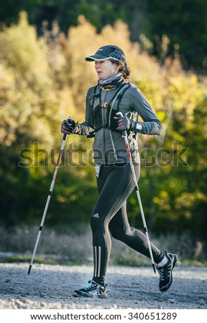 Yalta, Russia - October 31, 2015: young woman runner running marathon walking sticks during First Yalta mountain marathon