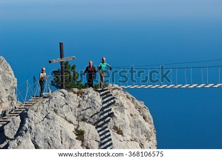 YALTA, RUSSIA - SEPTEMBER 19, 2015: People crossing the chasm on the rope bridge. Black sea background, Crimea, Russia