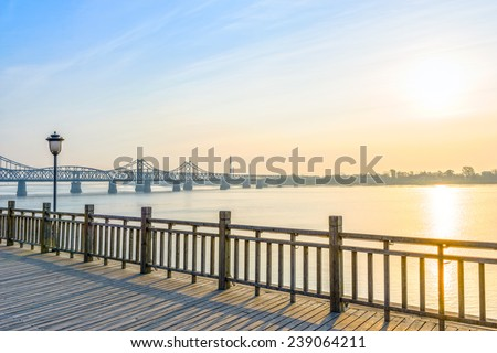 Yalu River Bridge at morning. In the distance is North Korea. Located in Yalu River Scenic Areas of Dandong City, Liaoning province, China.
