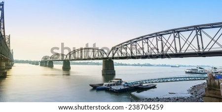 Yalu River Broken Bridge and Yalu River at morning. In the distance is North Korea. Located in Dandong City, Liaoning province, China.
