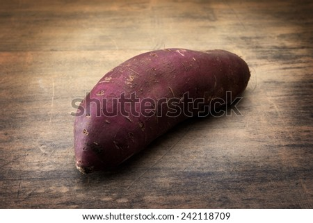 Yam, satsumaimo,or sweet potato on a old wooden surface.  - stock photo