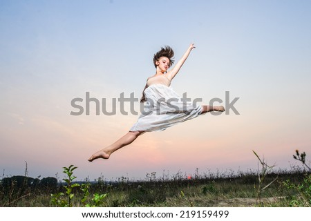 Yang female ballet dancer performs outdoor on sunset.