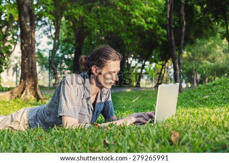 Yang freelance business man working outdoors on green meadow with laptop computer - stock photo