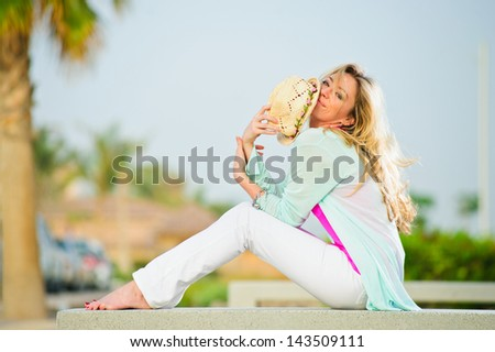 Yang pretty woman poses in stone bench in sunset time. - stock photo