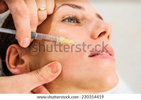 Yang woman getting botox injection. - stock photo