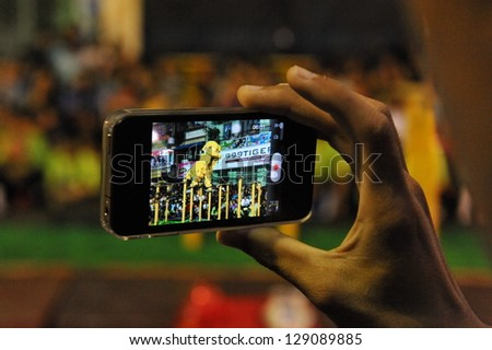 YANGON - FEB 11: A spectator uses a smartphone to video a lion dance on a downtown street during celebrations ushering in the Chinese new year of the snake on Feb 11, 2013 in Yangon, Burma. - stock photo