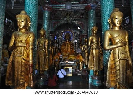 YANGON - FEB 12: Temple goers pray at Shwedagon Pagoda on Feb 12, 2013 in Yangon, Burma. Built between 6th and 10th century the landmark Shwedagon is considered Burma's most sacred Buddhist site. - stock photo