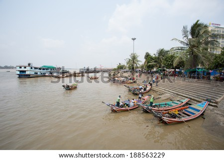 Yangon, Myanmar - April 6, 2014: A man navigates his boat full of passengers out of the busy Yangon port, Yangon is the largest city of Myanmar and the Port of Yangon is the country's most import port