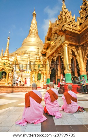 YANGON, MYANMAR - APRIL 13, 2012 : Three Burmese Buddhist nuns at the Shwedagon Pagoda, one of the most famous pagoda in the world and the main attraction of Yangon, Myanmar. - stock photo