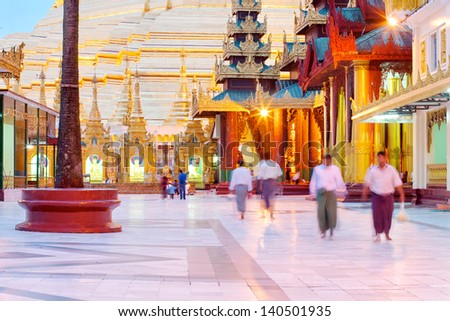 YANGON, MYANMAR (BURMA) - JUNE 25: Buddhist pilgrims walk in the Shwedagon Pagoda on June 25, 2011 in Yangon, Myanmar, Burma.  The centuries old pagoda is a one of the country's main tourist sites. - stock photo