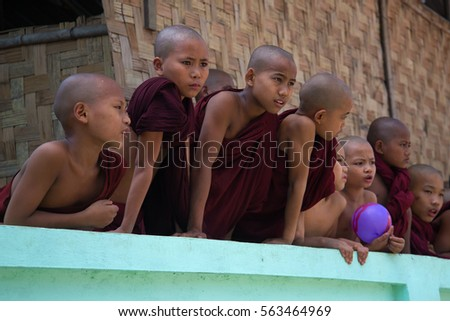 YANGON, MYANMAR - DECEMBER 18, 2016: Little novice monks look out from behind the fence of a Buddhist monastery