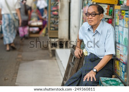 YANGON, MYANMAR - FEBRUARY 10: Burmese vendor waits for customers in Chinatown on February 10, 2014 in Yangon. Myanmar is ethnically diverse with 51 million inhabitants belonging to 135 ethnic groups. - stock photo