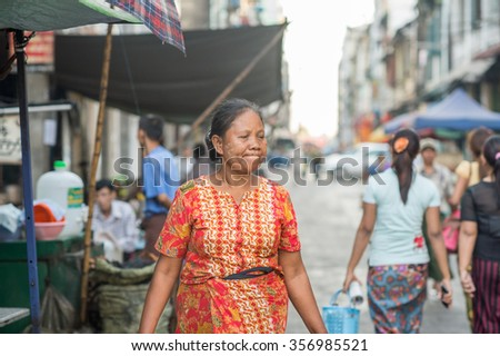 YANGON, MYANMAR â?? FEBRUARY 5: Burmese woman walks in Chinatown on February 5, 2014 in Yangon. Myanmar is ethnically diverse with 51 million inhabitants belonging to 135 ethnic groups.