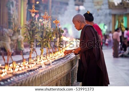 YANGON, MYANMAR - JAN 31: Buddhist devotees lighting candles at the full moon festival, Shwedagon Pagoda, January 31, 2010 in Myanmar (Burma). - stock photo