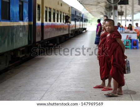 YANGON, MYANMAR- JULY 28: Two unidentified young novice monks waiting on the train at the Central Railway Station in Yangon, Myanmar on July 28, 2013. 89% of the Burmese population is Buddhist. - stock photo