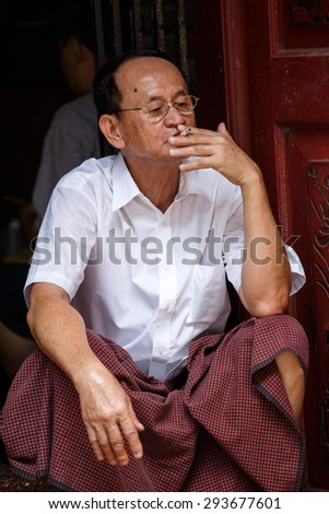 YANGON, MYANMAR - JUNE 12 2015: Chinese man smoking on one of the hottest recorded days before monsoon season in Yangon, Myanmar. - stock photo