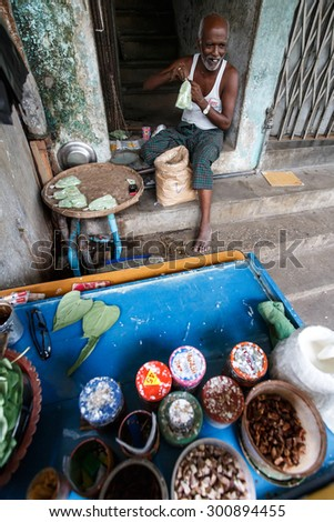 YANGON, MYANMAR - JUNE 12 2015: Local man making sweet snack on one of the hottest recorded days before monsoon season in Yangon, Myanmar. - stock photo