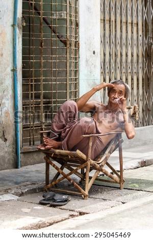 YANGON, MYANMAR - JUNE 12 2015: Old man smoking burmese cheroot cigar on one of the hottest recorded days before monsoon season in Yangon, Myanmar. - stock photo