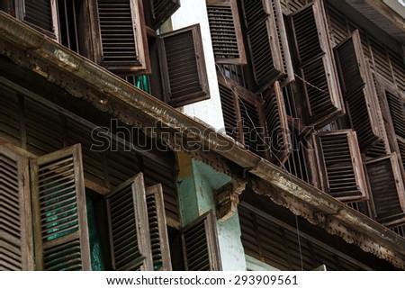 YANGON, MYANMAR - JUNE 12 2015: Rustic wooden window shutters open on one of the hottest recorded days before monsoon season in Yangon, Myanmar. - stock photo