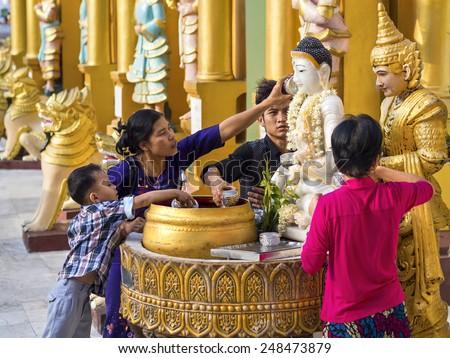 Yangon, Myanmar - March 5: Buddhist devotees bathing Buddha statue for blessings at Shwedagon Pagoda in Yangon, Myanmar (Burma). - stock photo