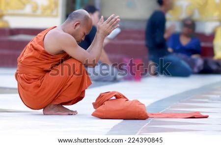 YANGON, MYANMAR - NOV 15: An unidentified buddhist monk kneels down in prayer on Nov 15, 2011 in Yangon, Myanmar - stock photo