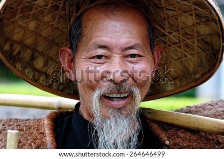 "Yangshuo, China - April 29, 2008:  Smiling Chinese ""bird man"" of Yanshuo wearing a straw hat with a bamboo pole resting on his shoulder"