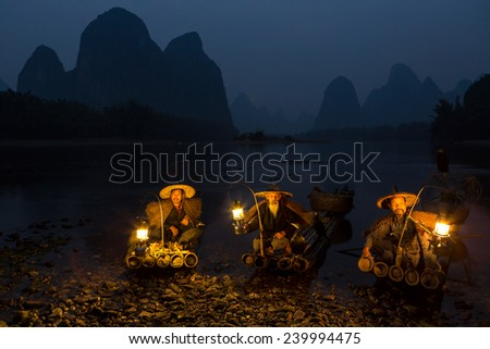 YANGSHUO, CHINA - OCTOBER 16: Chinese fishermans fishing with cormorants birds in Yangshuo, traditional fishing use trained cormorants to fish, October 16, 2013 Yangshuo in Guangxi region, China - stock photo