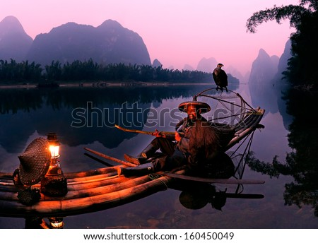 YANGSHUO - OCTOBER 16: Chinese fisherman fishing with cormorants birds in Yangshuo, Guangxi region, traditional fishing use trained cormorants to fish, October 16, 2013 Yangshuo in Guangxi, China  - stock photo