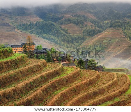 Yao Dazhai, Longsheng, near town of Guilin, Guangxi Province, China. Hillside rice terraces, rice fields in  highlands of Asia. Spring fog in mountains of southwestern China, rice terraces, farmhouses - stock photo