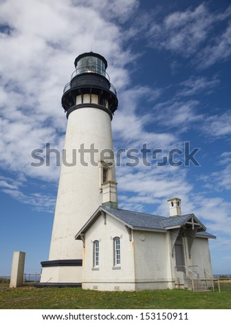 Yaquina Head Black and White Lighthouse Looking Up to Blue Sky With Dramatic Clouds