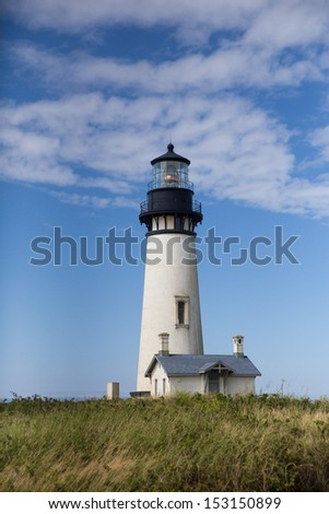 Yaquina Head Black and White Lighthouse with Blue Sky and White Puffy Clouds