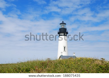 Yaquina Head Lighthouse and meadow against a partly cloudy sky at the Yaquina Head Outstanding Natural Area, Newport, Oregon. - stock photo
