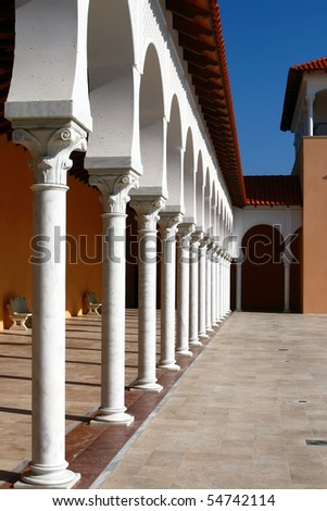 Yard and covered gallery of the  modern building in Spanish style. White columns, red tiles, blue sky.Caesarea, Israel