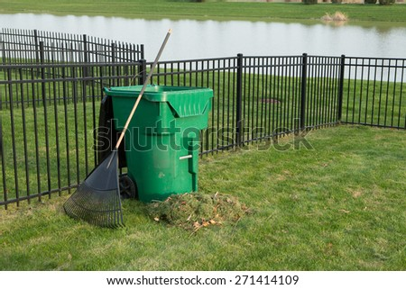 Yard maintenance in spring with a fresh heap of grass clippings and a rake leaning on a green plastic bin for composting organic waste on a neat lawn with wrought iron fence above a lake - stock photo