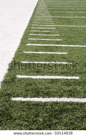 yard markers on the turf of an american football field - stock photo