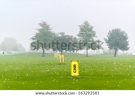 Yard signs in driving range and golf balls - stock photo