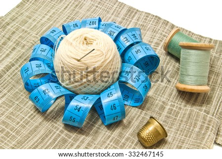 yarn and spools of thread on fabric - stock photo