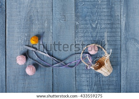 Yarn balls and basket. Knitwork background. Art craft, hand made. Handiwork, knitting, needlework. Wicker basket with woolen pink and orange balls at blue rustic wood background, top view, flat lay. - stock photo