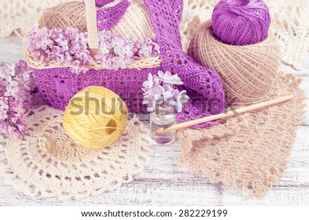 Yarn for crochet and knitted openwork napkins with lilac on shabby wooden boards - stock photo