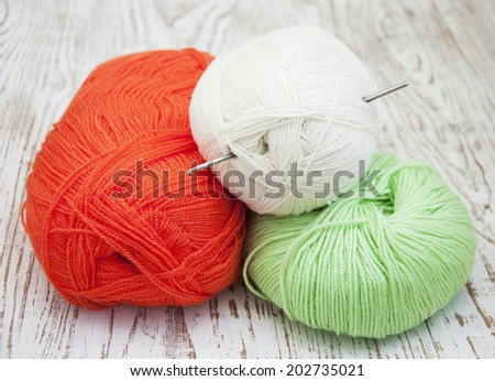 yarns and crotchet hook on a wooden background - stock photo