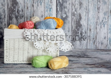 Yarns for knitting with napkin   in wicker basket  on wooden background