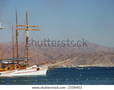 yatchs at the sea with desert mountains in the background - stock photo