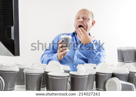 Yawning and tired businessman at office - stock photo