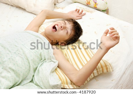 Yawning awaking boy on the bed at the early morning - stock photo